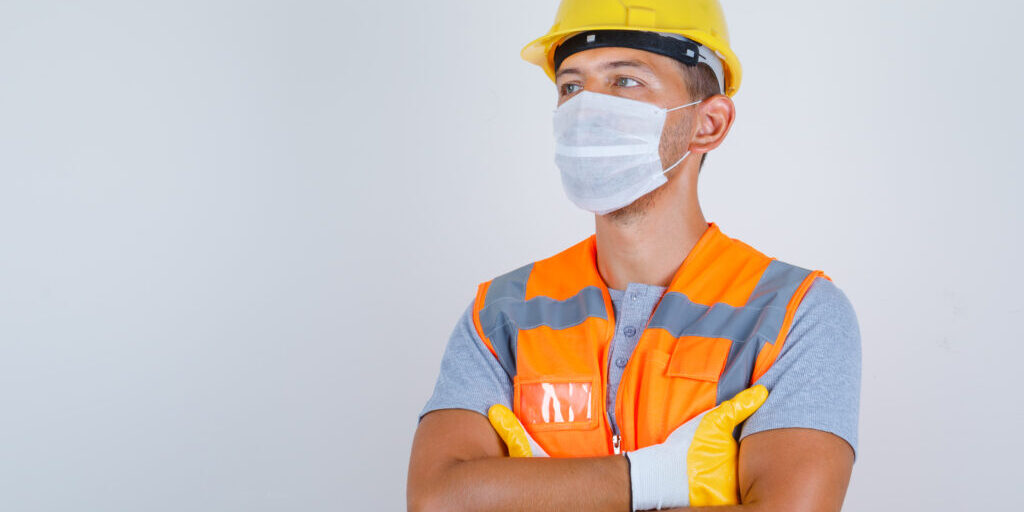 Male builder in uniform, helmet, gloves, mask looking away with crossed arms and looking careful , front view.